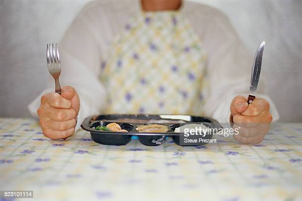Man with Knife and Fork Sitting next to TV Dinner