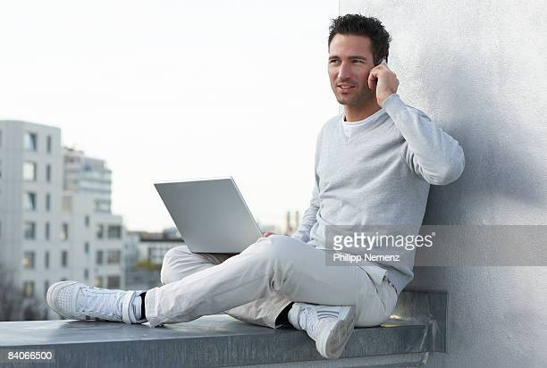man with laptop and cellphone sitting on rooftop