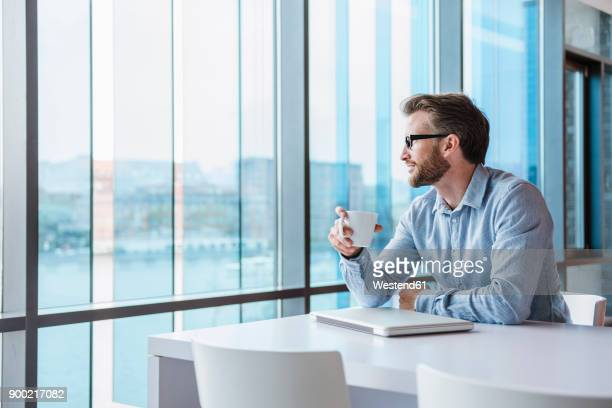 Man with laptop and coffee cup sitting in modern office building