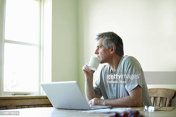 Man with laptop and coffee looking out of window