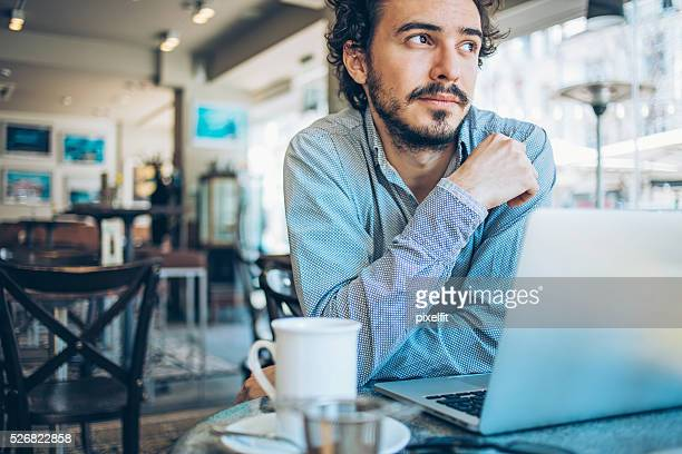 man with laptop and hot drink in a restaurant - impatient stock pictures, royalty-free photos & images