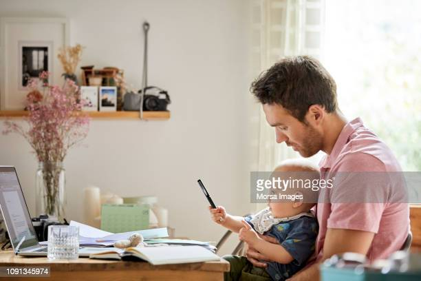 man with laptop and papers looking at playful son - responsibility stock pictures, royalty-free photos & images