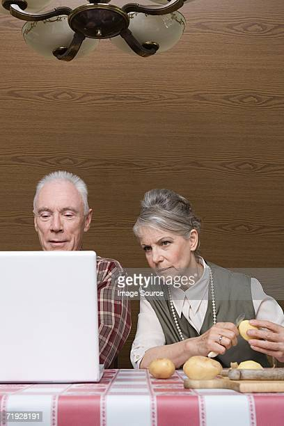 Man with laptop and wife with potatoes