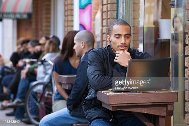 man with laptop at outdoor cafe