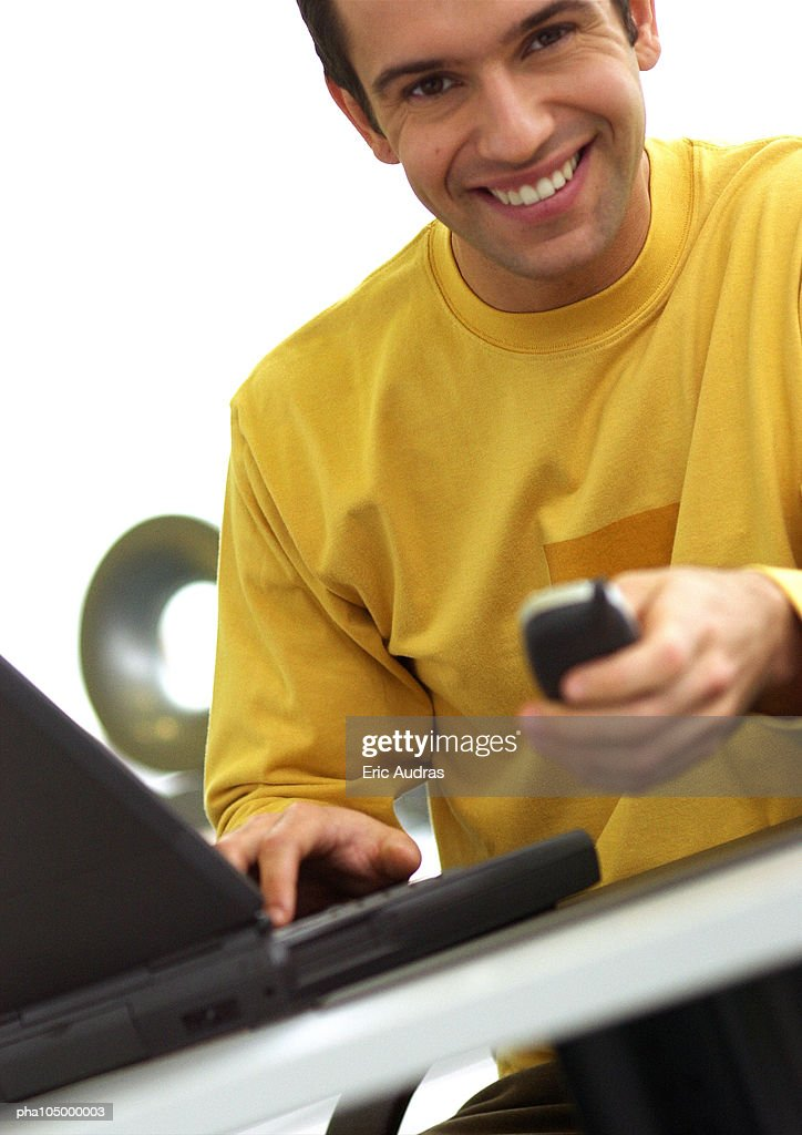 Man with laptop computer and cell phone, smiling : Stockfoto