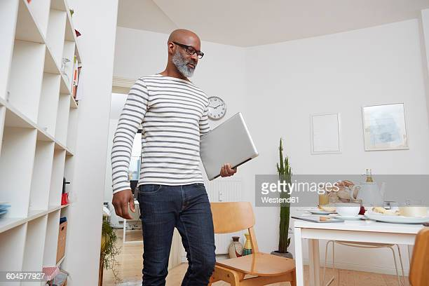 man with laptop in his kitchen at home - carrying stock pictures, royalty-free photos & images