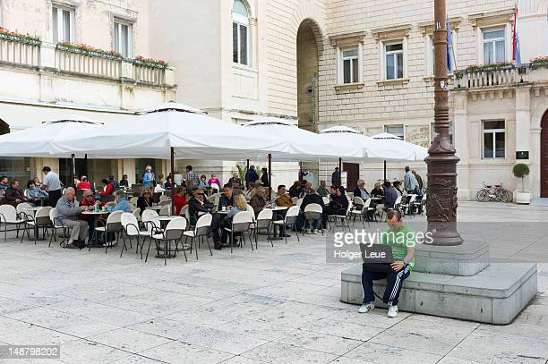 Man with laptop using free WiFi on town square with street cafe behind.