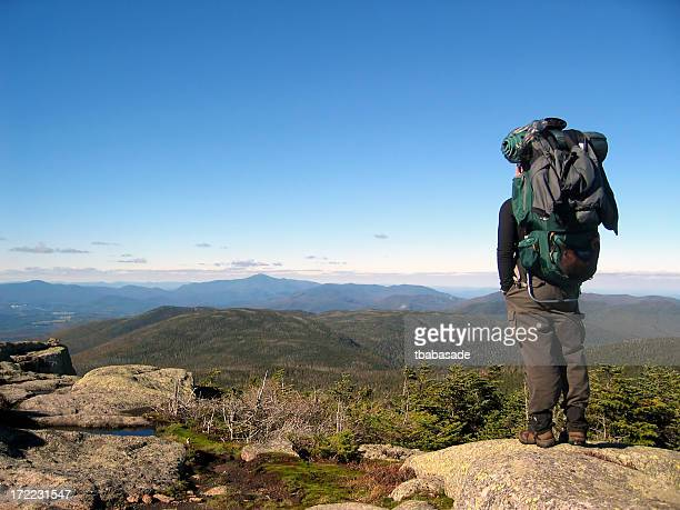 A man with large backpack standing atop a mountain
