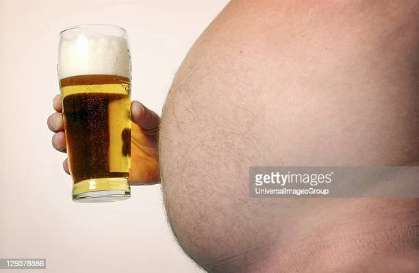 Man with large beer gut holding pint glass full of beer