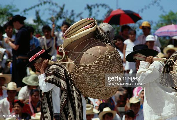 Man with large orci strapped on his back during a dance for the celebration at the Guelaguetza festival Oaxaca Mexico