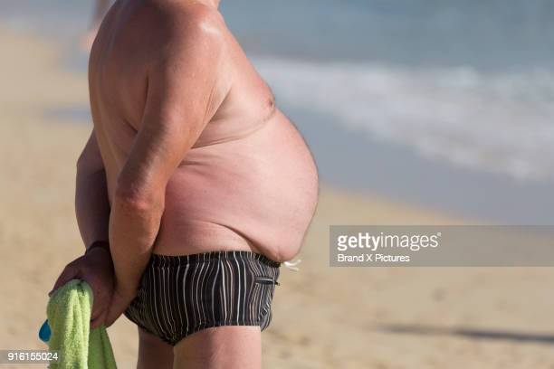 man with large stomach on the beach in morro jable in fuerteventura - fat man on beach stock photos and pictures