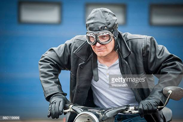 man with leather jacket sitting on vintage moped - moped stock photos and pictures