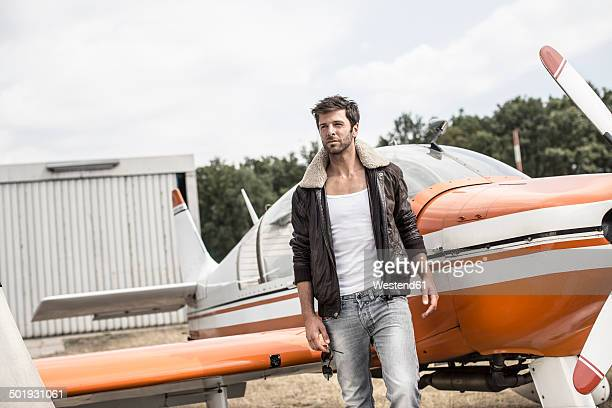 Man with leather jacket standing in front of propeller plane