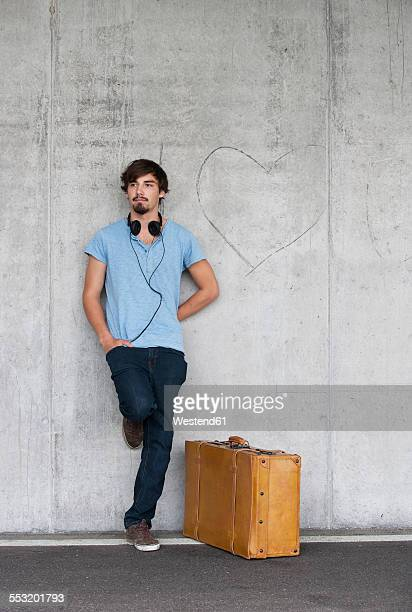 man with leather suitcase and headphones leaning at concrete wall - leaning stock pictures, royalty-free photos & images