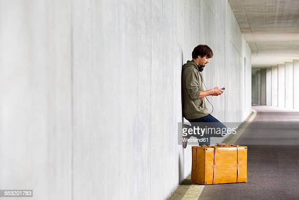Man with leather suitcase and smartphone waiting in a car park