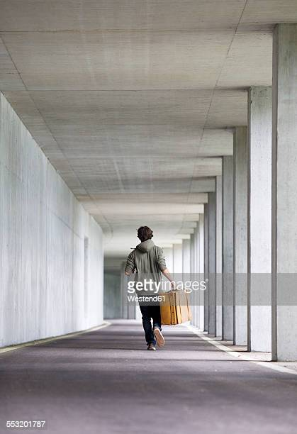 Man with leather suitcase running in a car park