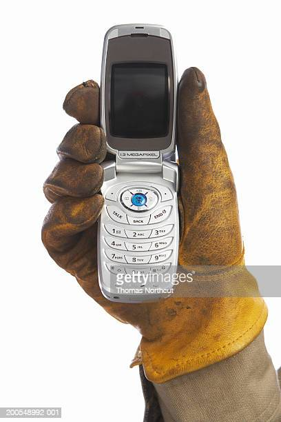 man with leather work glove holding cell phone, close-up of hand - work glove stock pictures, royalty-free photos & images