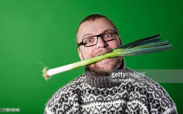 Man with leek in mouth