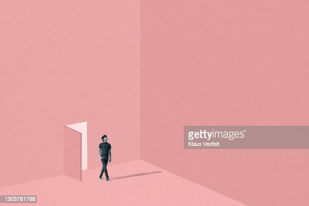 man with legs crossed standing against coral door - new stock pictures, royalty-free photos & images
