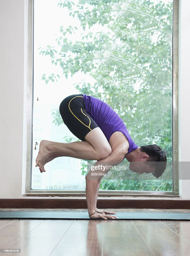 Man with legs off the ground and balancing in a yoga position in a yoga studio, side view : Stock Photo