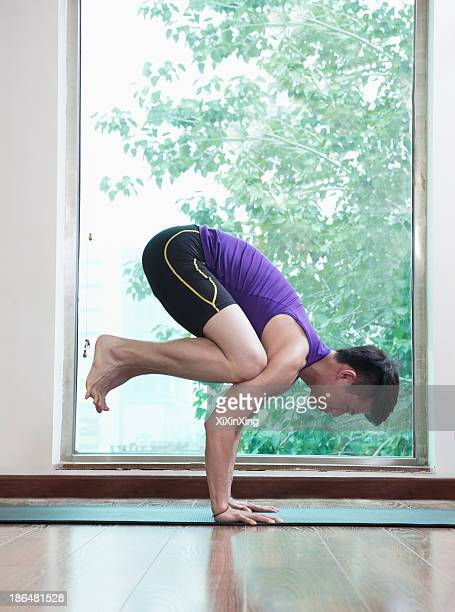Man with legs off the ground and balancing in a yoga position in a yoga studio, side view