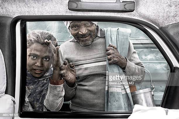 CONTENT] Man with leprosy and girl peer through a taxi window staring at passengers @ Kolkata intersection traffic light Kolkata INDIA