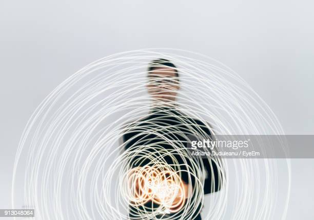 man with light painting against white background - lichtmalerei stock-fotos und bilder