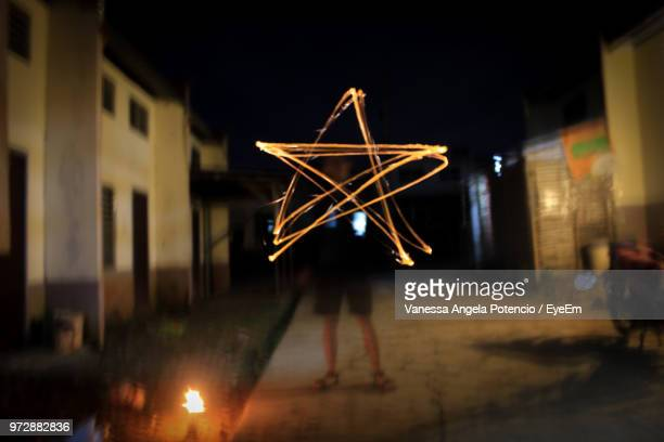 Man With Light Painting Standing In City At Night