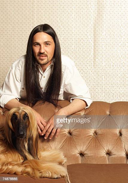man with long dark hair standing by afghan hound lying on sofa, portrait - mimica fotografías e imágenes de stock
