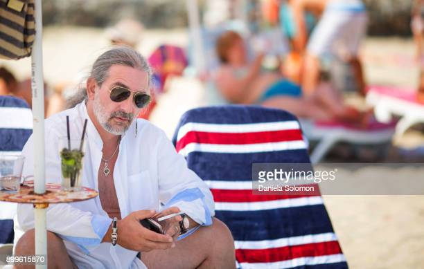 Man with long hair and beard on the beach sitting on a lounge chair