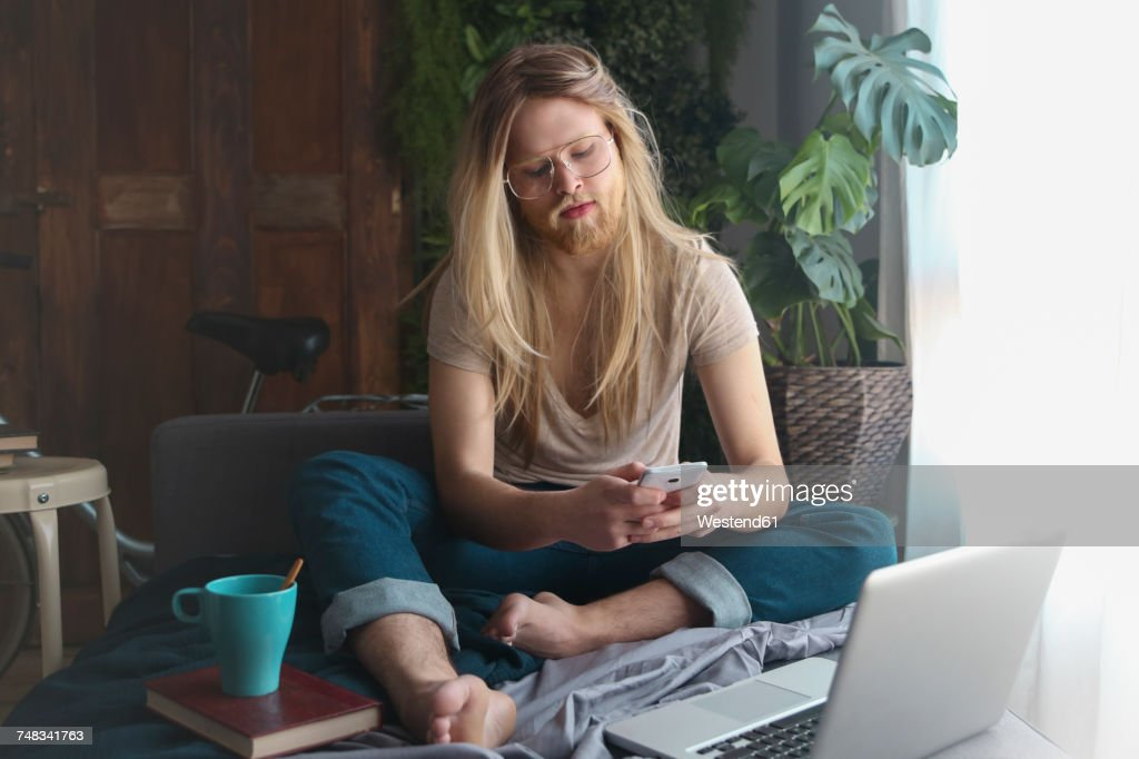 Man with long hair and beard sitting on sofa bed looking at smartphone : Foto de stock