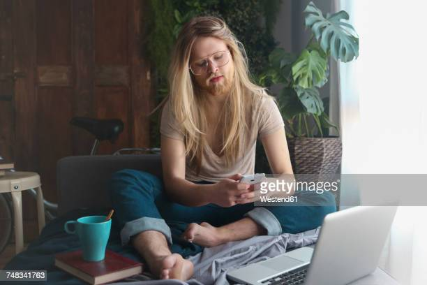 man with long hair and beard sitting on sofa bed looking at smartphone - lang haar stockfoto's en -beelden