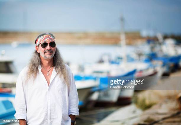 Man with long hair and beard standing in front of boats