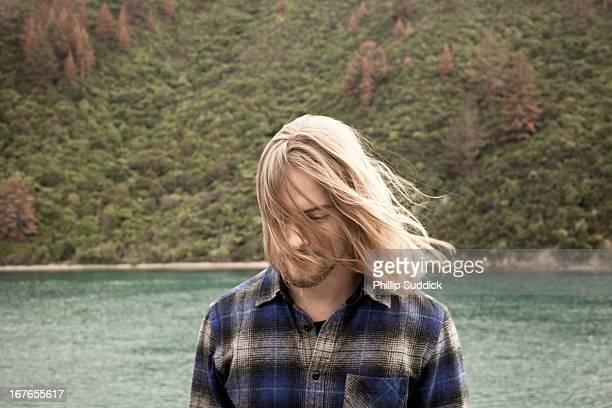 man with long hair looking down into ocean - langes haar stock-fotos und bilder