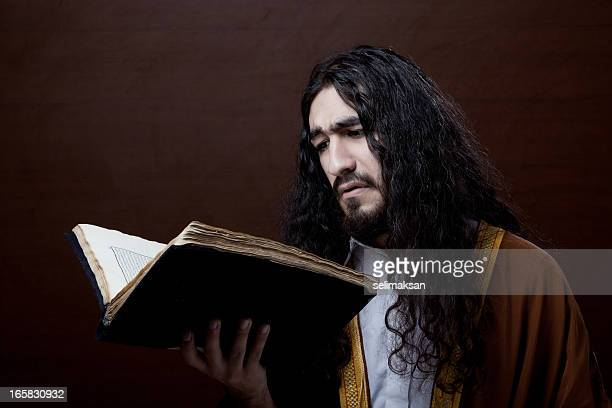 Man with long hair reading old antique book.