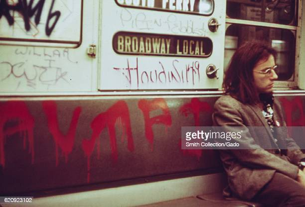 A man with long hair sits on a seat on a subway car which has been extensively marked with graffiti New York City New York May 1973 Image courtesy...