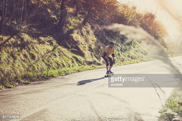 Man with longboard on country road