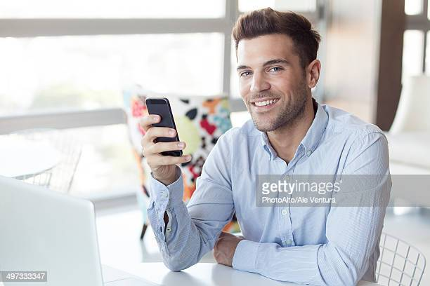 man with look of satisfaction holding smartphone - 襟付きシャツ ストックフォトと画像