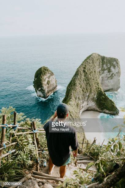 a man with looking at the ocean in bali - bali stock pictures, royalty-free photos & images