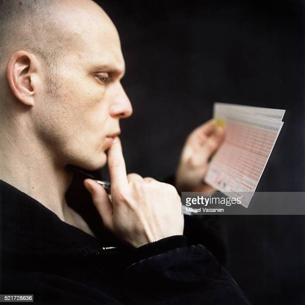 man with lottery ticket - lotterytickets stock pictures, royalty-free photos & images