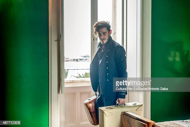 Man with luggage in bedroom