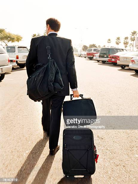 Man with luggage in parking lot