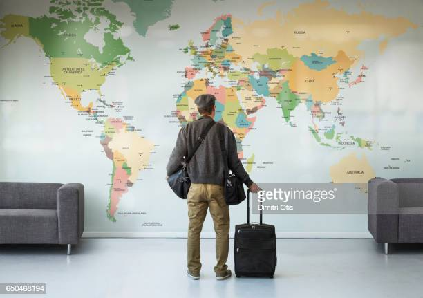 man with luggage looking at large wall map - karte navigationsinstrument stock-fotos und bilder