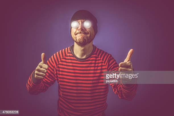 Homem com olhos luminosa com o polegar para cima