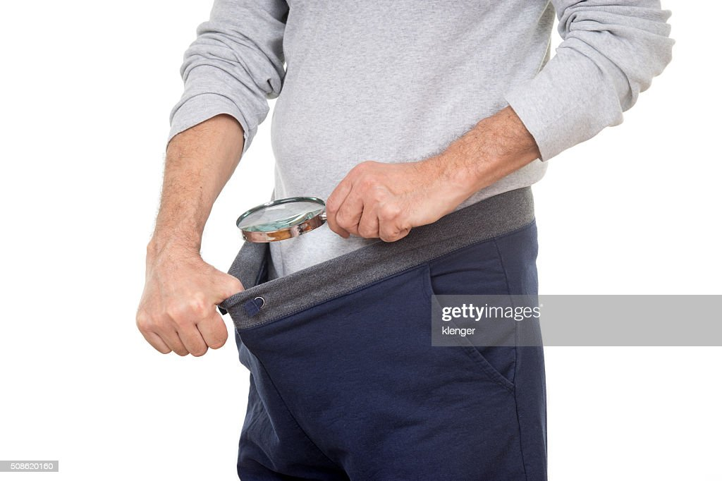 Man with magnifying glass looking into his tracksuit pants : Stock Photo