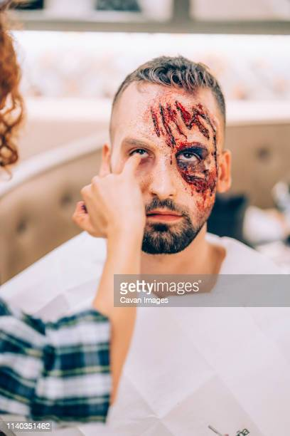 man with makeup on his face with wounds and blood. - zombie face stock photos and pictures