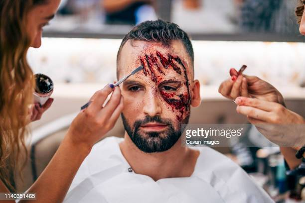 man with makeup on his face with wounds and blood. - zombie makeup stock photos and pictures