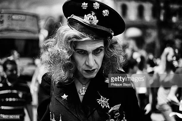 CONTENT] A man with makeup wearing a cop uniform with a severe behavior during the Gay Pride Festival in Paris 2013