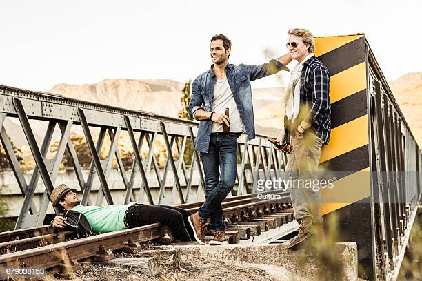 Man with male friends lying on rural railway bridge track, Franschhoek, South Africa