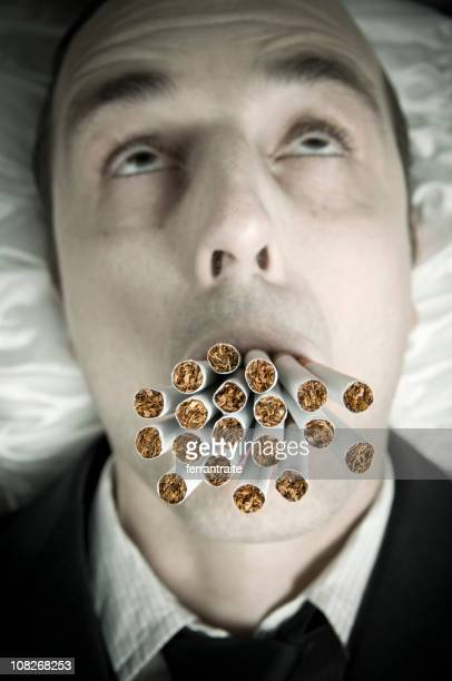 man with many cigarettes in mouth - self harm stock photos and pictures